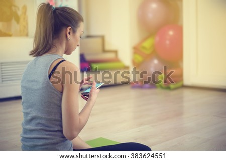 Woman in the fitness gym. She holds the mobile phone during a break, or before exercise. - stock photo