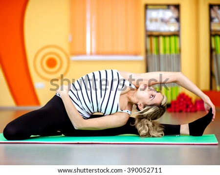 Woman in the gym with a dumbbell makes charging - stock photo