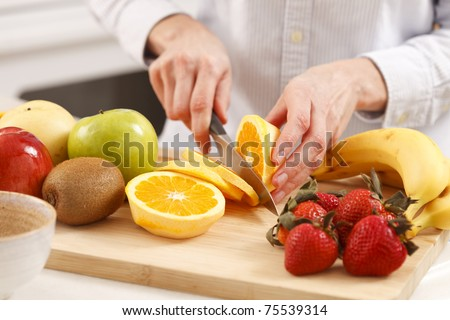 Woman in the kitchen cutting fruits - stock photo