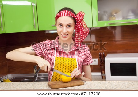 Woman in the kitchen is cutting a fresh lemon