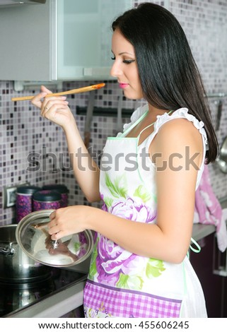 Woman in the kitchen tasting food from a spoon