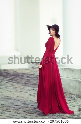 Woman in the long red dress looking back - stock photo