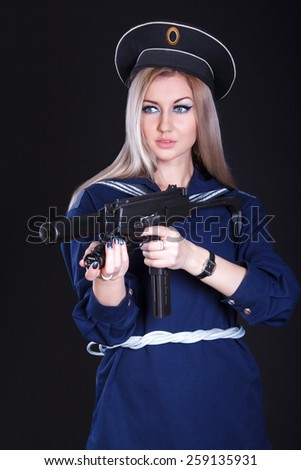 Woman in the marine uniform with a submachine gun over black background - stock photo