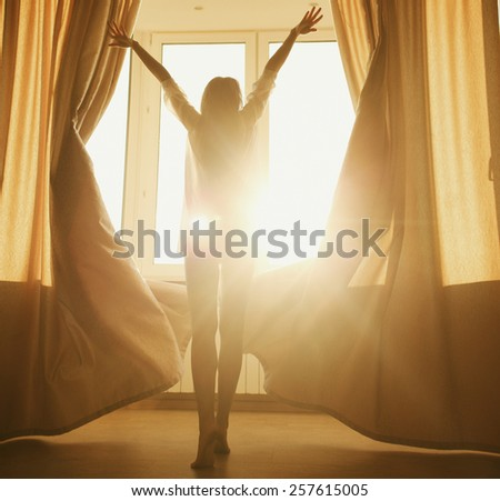 Woman in the morning. Attractive sexy woman with slender body is looking at the sunrise standing near the window in her home and having a perfect cozy morning. - stock photo