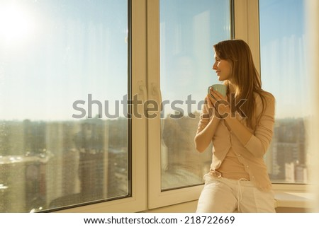 Woman in the morning. Attractive tender young woman is holding a cup with hot tea or coffee and looking at the sunrise sitting near the window in her home and having a perfect cozy morning. - stock photo