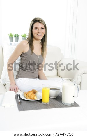 woman in the morning in his sofa, ready to have breakfast - stock photo