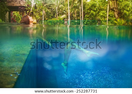 woman in the pool, underwater view - stock photo