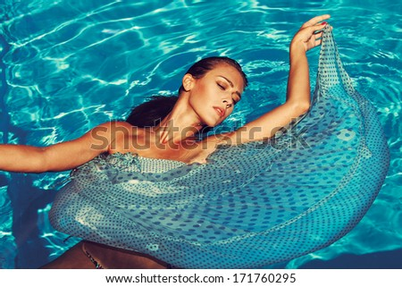 woman in the pool wearing blue dress  - stock photo