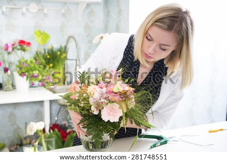 Woman in the process of boquet composition - stock photo