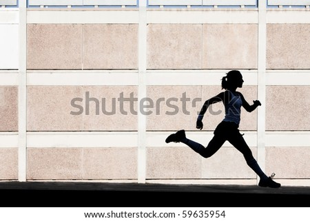 Woman in the shadows of building runs for exercise. - stock photo