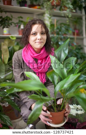 woman in the shop surrounded by different flowers - stock photo