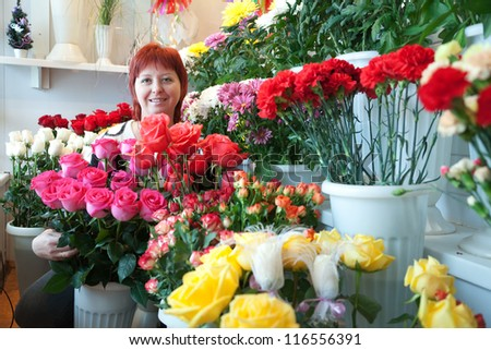 woman in the store surrounded by different flowers - stock photo