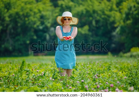 Woman in the straw hat holds strawberry in the hands - stock photo