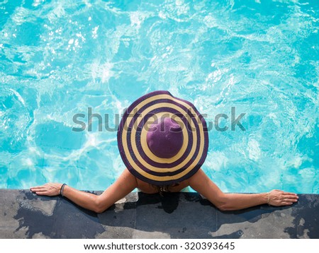 Woman in the swimming pool at tropical resort in Asia - stock photo