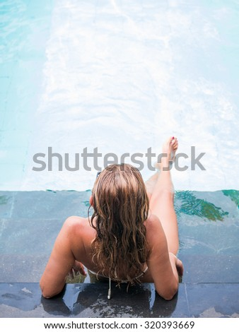Woman in the swimming pool at tropical resort in Asia