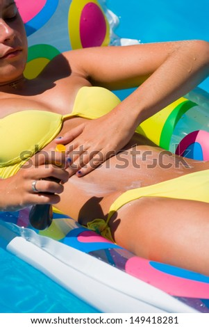 Woman in the swimming pool putting solar cream  Motion blur - stock photo
