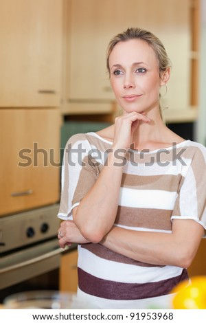 Woman in thoughts standing in the kitchen - stock photo