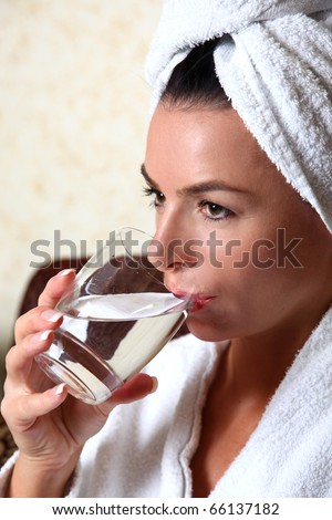woman in towel drinking water - stock photo