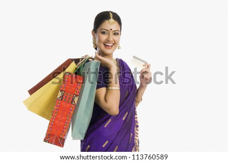 Woman in traditional Assamese dress holding shopping bags with a credit card and smiling - stock photo