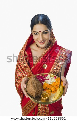 Woman in traditional Assamese mekhla holding religious offering