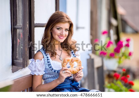 Woman in traditional bavarian dress holding pretzel, country hou