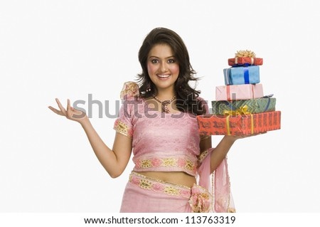 Woman in traditional Indian dress holding gifts and smiling - stock photo