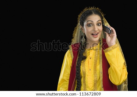 Woman in traditional Punjabi dress using a mobile phone - stock photo