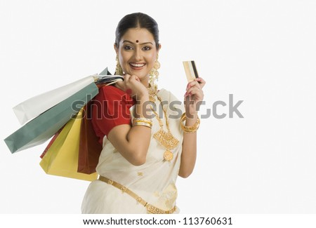Woman in traditional South Indian sari holding shopping bags with a credit card and smiling - stock photo