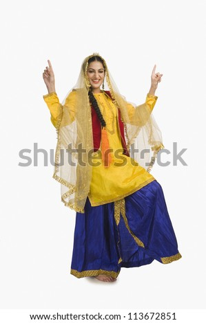 Woman in traditional yellow Punjabi dress doing bhangra - stock photo