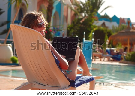 woman in tropical hotel with laptop