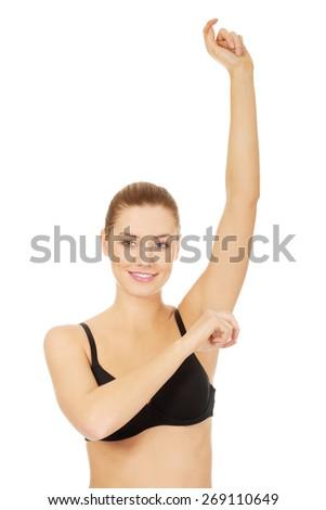Woman in underwear applying antiperspirant. - stock photo