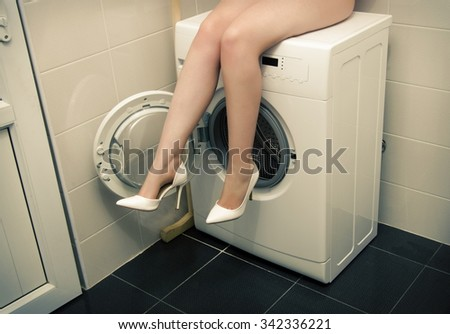 Woman in underwear in the bathroom sitting on washing machine