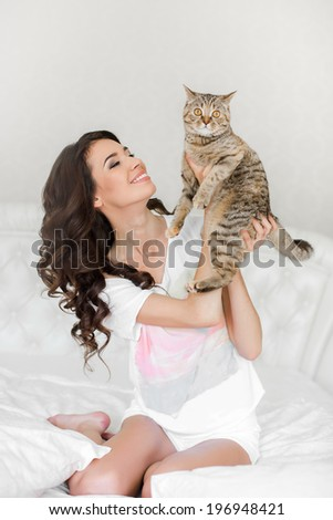 Woman in underwear relaxing and playing on bed with her cat on the summer warm day. - stock photo