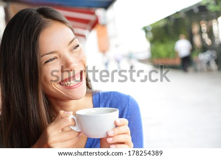 Woman in Venice, Italy at cafe drinking coffee on vacation travel. Smiling happy Mixed race Asian Caucasian girl having fun laughing on Italian sidewalk cafe during holidays in Venice, Italy, Europe. - stock photo