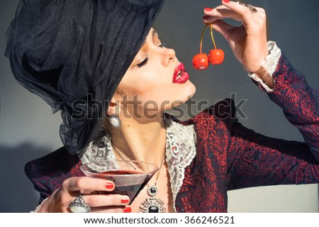 Woman in vintage black hat and jacket, drinking a martini with a cherry - stock photo