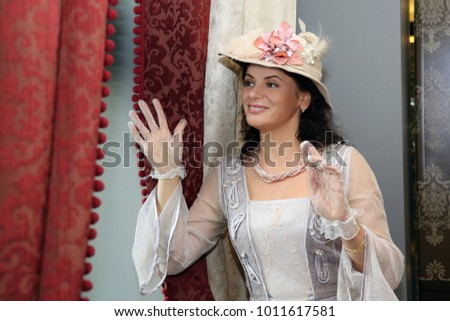 Woman in vintage dress and hat looks out the window smiling