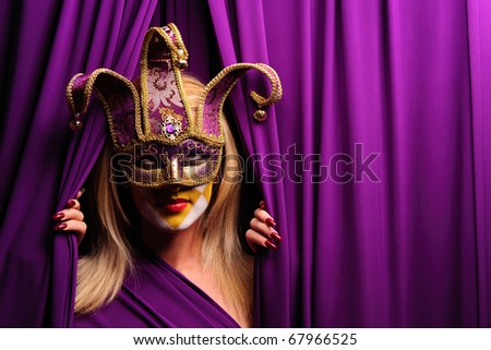 woman in violet mask opening curtain, may be use for theater concept - stock photo