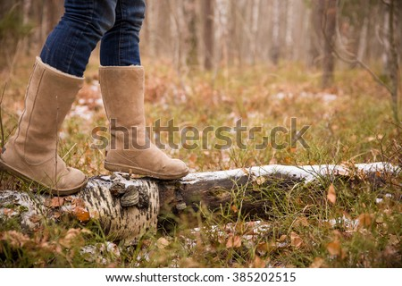 Woman in warm boots on the old log with first snow in the forest. Walking in the winter park. Outdoors winter activities.