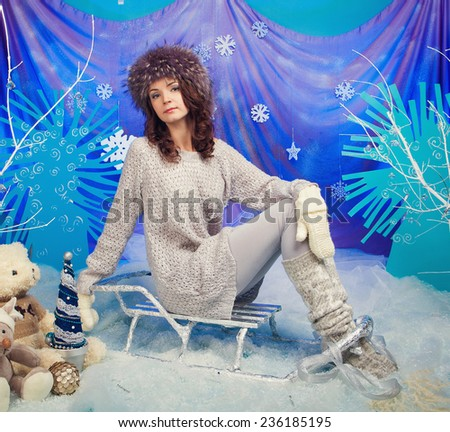 Woman in warm gloves on sled on a blue background - stock photo