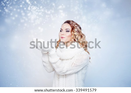Woman  in  warm knitted scarf and gloves happy snowfall ,  catching snowflakes on hands.  - stock photo