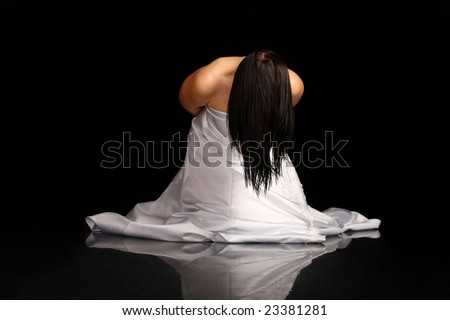 Woman in wedding dress on her knees. Isolated on black background.