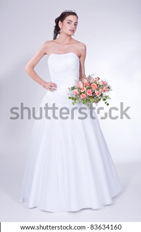 Woman in wedding dress with flowers' bouquet.