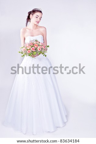 Woman in wedding dress with flowers' bouquet. - stock photo