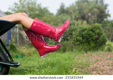 Woman in welly boots in wheelbarrow at home in the garden - stock photo