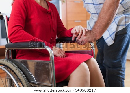 woman in   wheelchair and   elderly man near