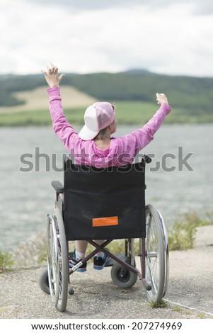 woman in wheelchair enjoying outdoors beach  - stock photo