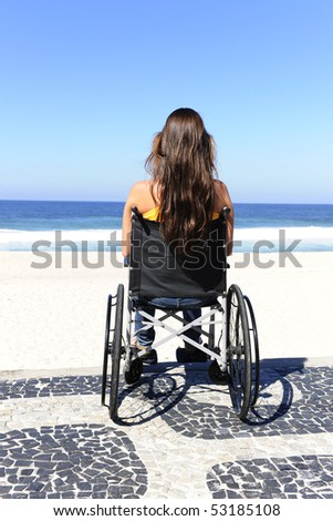 woman in wheelchair  enjoying outdoors beach, rear view - stock photo