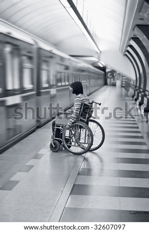 Woman in wheelchair missed the train in subway. - stock photo