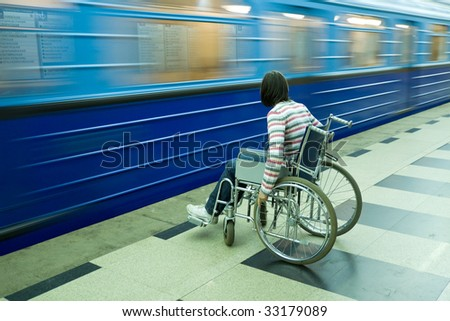 Woman in wheelchair near to passing train of subway - stock photo