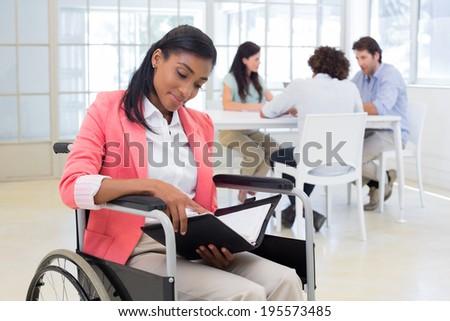 Woman in wheelchair reading document with colleauges in background in the office - stock photo